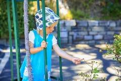 Kleines blondes behaartes Mädchen in einem Hut ermüdet Buschblätter Lizenzfreies Stockbild