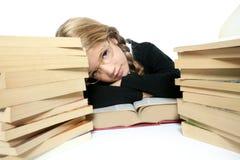 Kleines blondes gebohrtes Kursteilnehmermädchen, das auf Buch denkt Stockbild