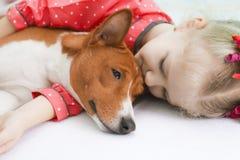 Kleines blondes gelocktes Mädchen, das einen roten basenji Hund umarmt Lizenzfreies Stockbild