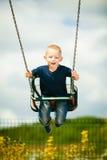 Kleines blondes Jungenkind, das Spaß auf einem Schwingen im Freien hat Lizenzfreie Stockfotografie
