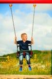 Kleines blondes Jungenkind, das Spaß auf einem Schwingen im Freien hat Lizenzfreies Stockbild