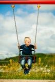 Kleines blondes Jungenkind, das Spaß auf einem Schwingen im Freien hat Stockfotos