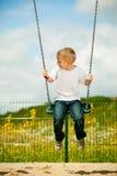 Kleines blondes Jungenkind, das Spaß auf einem Schwingen im Freien hat Lizenzfreie Stockfotos