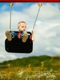 Kleines blondes Jungenkind, das Spaß auf einem Schwingen im Freien hat Stockfoto