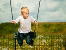 Kleines blondes Jungenkind, das Spaß auf einem Schwingen im Freien hat Stockfotografie