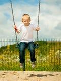 Kleines blondes Jungenkind, das Spaß auf einem Schwingen im Freien hat Lizenzfreies Stockfoto