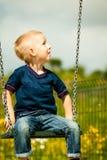 Kleines blondes Jungenkind, das Spaß auf einem Schwingen im Freien hat Stockbilder