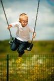 Kleines blondes Jungenkind, das Spaß auf einem Schwingen im Freien hat Stockbild