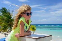 Kleines blondes kaukasisches Mädchen in der Sonnenbrille ist auf dem Strand Blauer Himmel, Ozean und Palmen sind als Hintergrund Lizenzfreie Stockfotos
