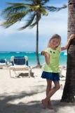 Kleines blondes kaukasisches Mädchen hält Nüsse auf dem karibischen Strand Palmen, blauer Ozean und Himmel sind als Hintergrund Lizenzfreie Stockfotografie