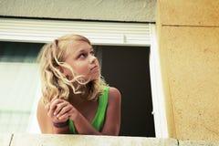 Kleines blondes kaukasisches Mädchen im Fenster Lizenzfreie Stockfotos