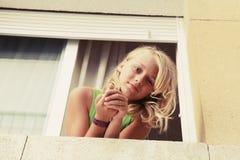 Kleines blondes kaukasisches Mädchen im Fenster Stockfotos