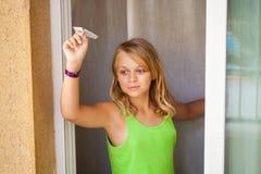 Kleines blondes kaukasisches Mädchen mit kleiner Papierfläche im Fenster Stockbild