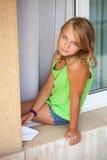 Kleines blondes kaukasisches Mädchen mit Papierfläche im Fenster Stockfotos