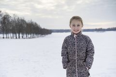 Kleines blondes kaukasisches schwedisches Mädchen, das in der lächelnden und lachenden Winterlandschaft im Freien steht Lizenzfreies Stockfoto