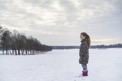 Kleines blondes kaukasisches schwedisches Mädchen, das in der skandinavischen Winterlandschaft im Freien steht Lizenzfreies Stockfoto