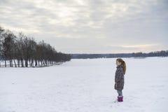 Kleines blondes kaukasisches schwedisches Mädchen, das in der Winterlandschaft im Freien steht Stockbild