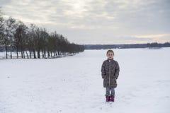Kleines blondes kaukasisches schwedisches Mädchen, das in der Winterlandschaft im Freien steht Stockfotos