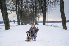 Kleines blondes kaukasisches schwedisches Mädchen, das mit Hund an der Straße in der Wintergasse sitzt Lizenzfreies Stockbild