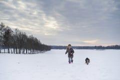 Kleines blondes kaukasisches schwedisches Mädchen, das mit Hund in der Winterlandschaft läuft und spielt Stockfotografie