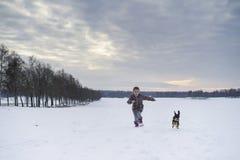 Kleines blondes kaukasisches schwedisches Mädchen, das mit Hund in der Winterlandschaft läuft und spielt Lizenzfreies Stockfoto