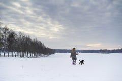 Kleines blondes kaukasisches schwedisches Mädchen, das mit Hund in der Winterlandschaft spielt Lizenzfreies Stockfoto