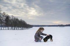 Kleines blondes kaukasisches schwedisches Mädchenspielen und -umarmungshündchen in der schwedischen Winterlandschaft Stockfotos