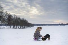 Kleines blondes kaukasisches schwedisches Mädchenspielen und -umarmungshündchen in der Winterlandschaft Stockbilder