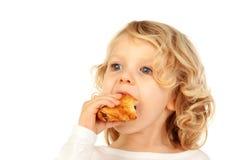 Kleines blondes Kind, das ein Hörnchen isst Lizenzfreies Stockfoto