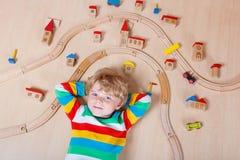 Kleines blondes Kind, das mit der hölzernen Eisenbahn Innen spielt Stockfotos
