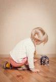 Kleines blondes Kind, das mit Sphynx-Kätzchen spielt Stockfoto