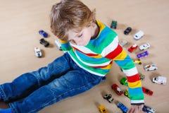 Kleines blondes Kind, das mit vielen Spielzeugautos Innen spielt Lizenzfreies Stockbild