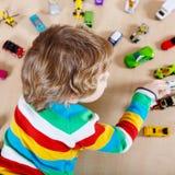 Kleines blondes Kind, das mit vielen Spielzeugautos Innen spielt Stockfotos
