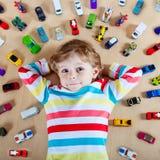 Kleines blondes Kind, das mit vielen Spielzeugautos Innen spielt Lizenzfreie Stockfotos