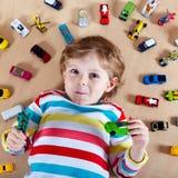 Kleines blondes Kind, das mit vielen Spielzeugautos Innen spielt Stockbild