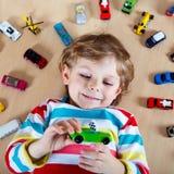 Kleines blondes Kind, das mit vielen Spielzeugautos Innen spielt Lizenzfreies Stockfoto