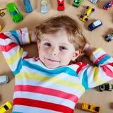 Kleines blondes Kind, das mit vielen Spielzeugautos Innen spielt Lizenzfreie Stockbilder