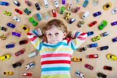 Kleines blondes Kind, das mit vielen Spielzeugautos spielt Lizenzfreies Stockfoto