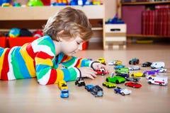 Kleines blondes Kind, das mit vielen Spielzeugautos spielt Stockbild