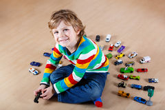 Kleines blondes Kind, das mit vielen Spielzeugautos spielt Lizenzfreie Stockfotografie