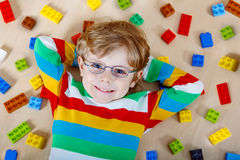 Kleines blondes Kind, das mit vielen von buntem spielt Lizenzfreie Stockbilder