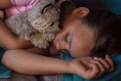 Kleines blondes Kind, das in seinem Bett mit Spielzeug schläft Lizenzfreies Stockfoto