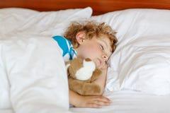 Kleines blondes Kind, das in seinem Bett mit Spielzeug schläft Lizenzfreie Stockfotografie