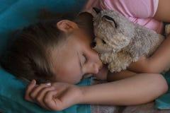 Kleines blondes Kind, das in seinem Bett mit Spielzeug schläft Stockfotos