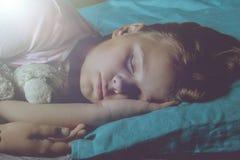 Kleines blondes Kind, das in seinem Bett mit Spielzeug schläft Stockfoto