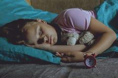 Kleines blondes Kind, das in seinem Bett mit Spielzeug schläft Lizenzfreie Stockbilder