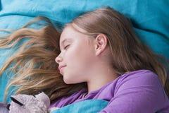 Kleines blondes Kind, das in seinem Bett mit Spielzeug schläft Stockbild