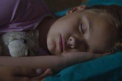 Kleines blondes Kind, das in seinem Bett mit Spielzeug schläft Stockfotografie