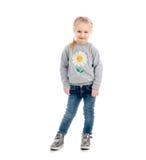 Kleines blondes Kind, das ungeschickt, lokalisiert lächelt Stockfotografie