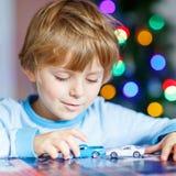 Kleines blondes Kind, das zu Hause mit Autos und Spielwaren spielt Lizenzfreie Stockbilder